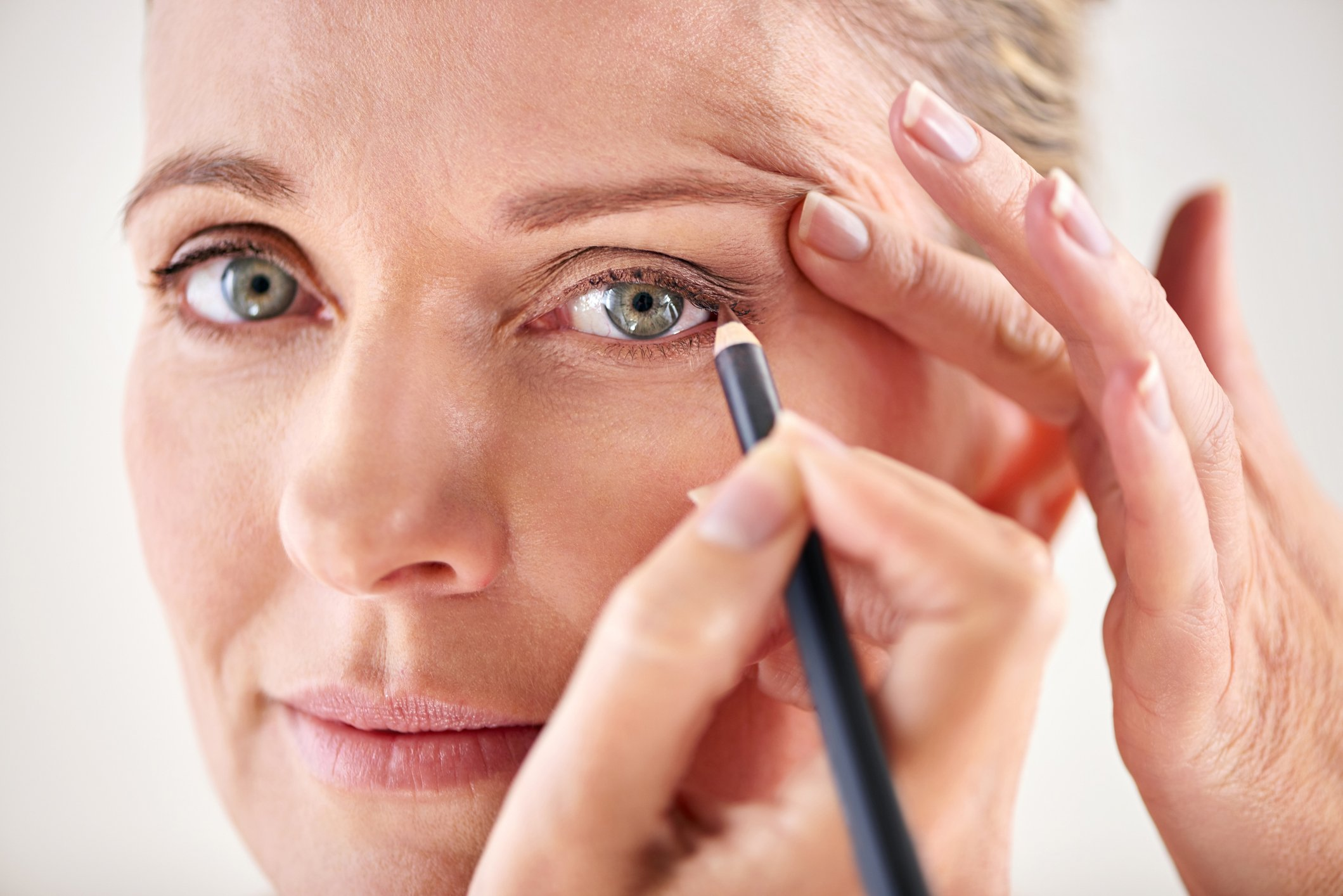 shot of a mature woman applying eyeliner