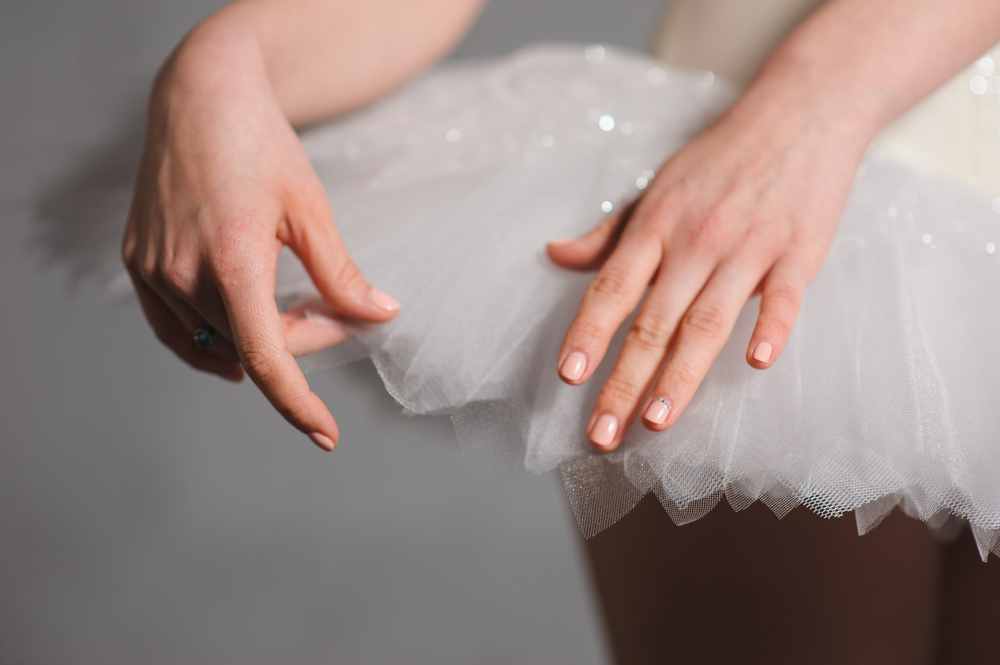 Close-up. hands ballerina on a background of white tutu.