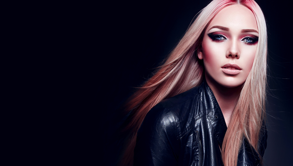 Beautiful blonde girl in black leather jacket and pink hair in rock style on black background.