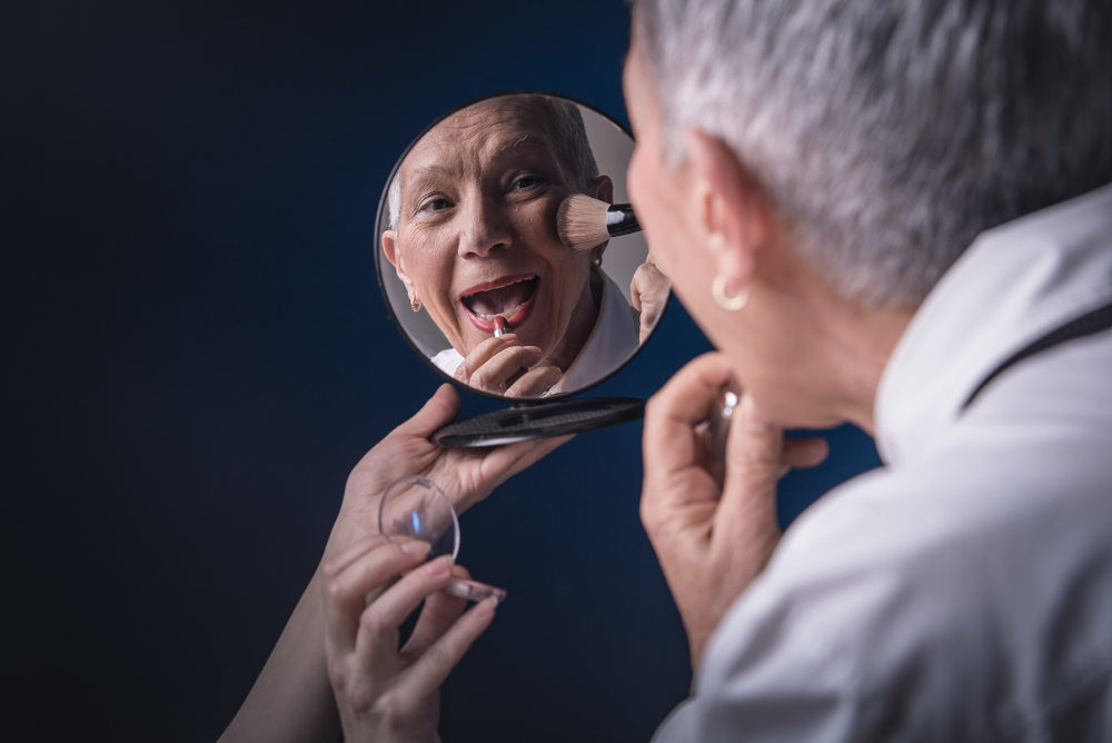 Senior elderly woman applying make up, looking herself at a hand mirror