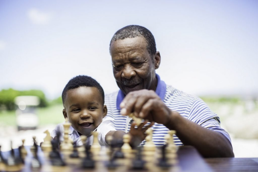 senior with young boy chess