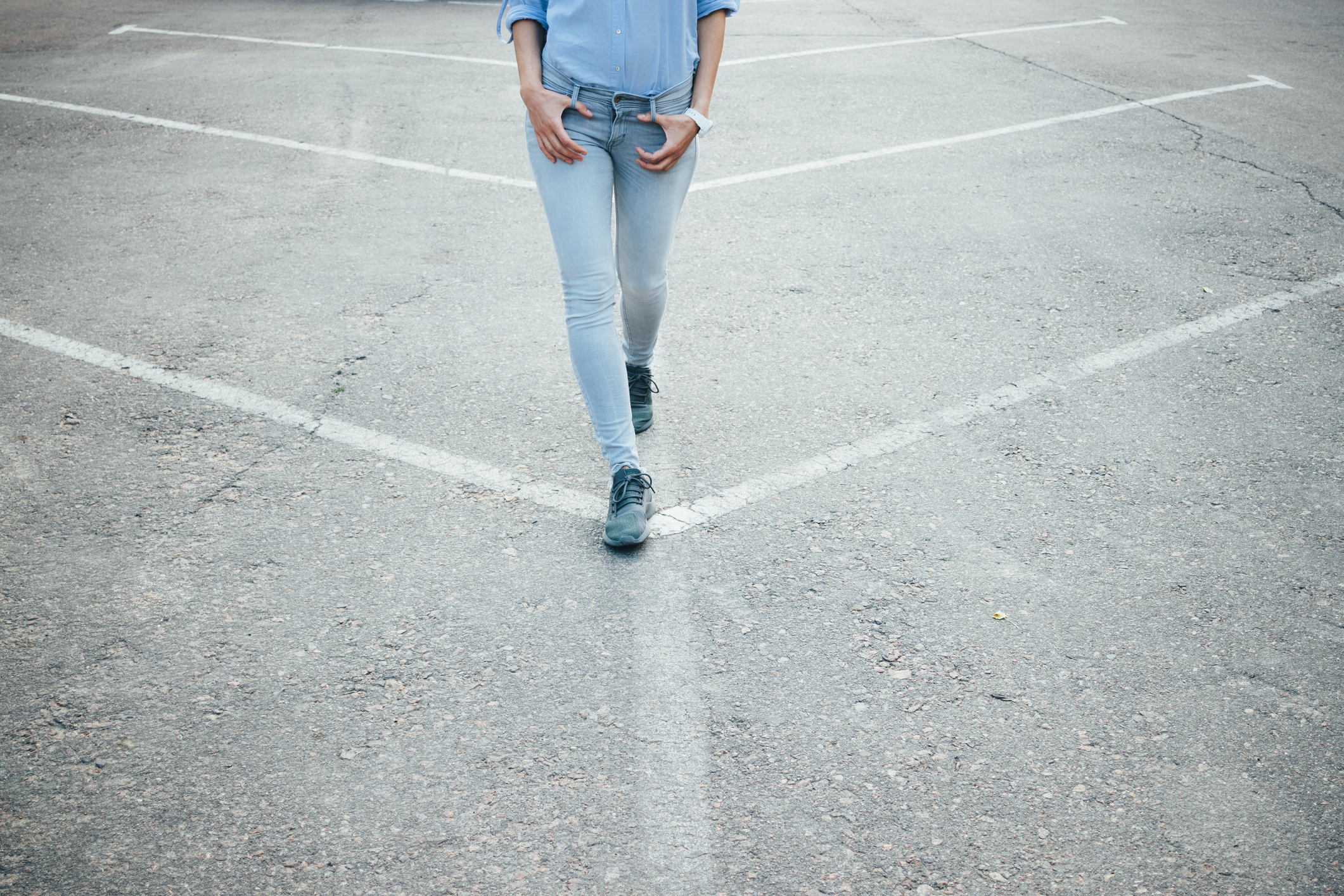 Unrecognizable young slender woman dressed in gray jeans and a blue shirt walks relaxed on empty asphalt street. Female's legs stepping in city, close-up.