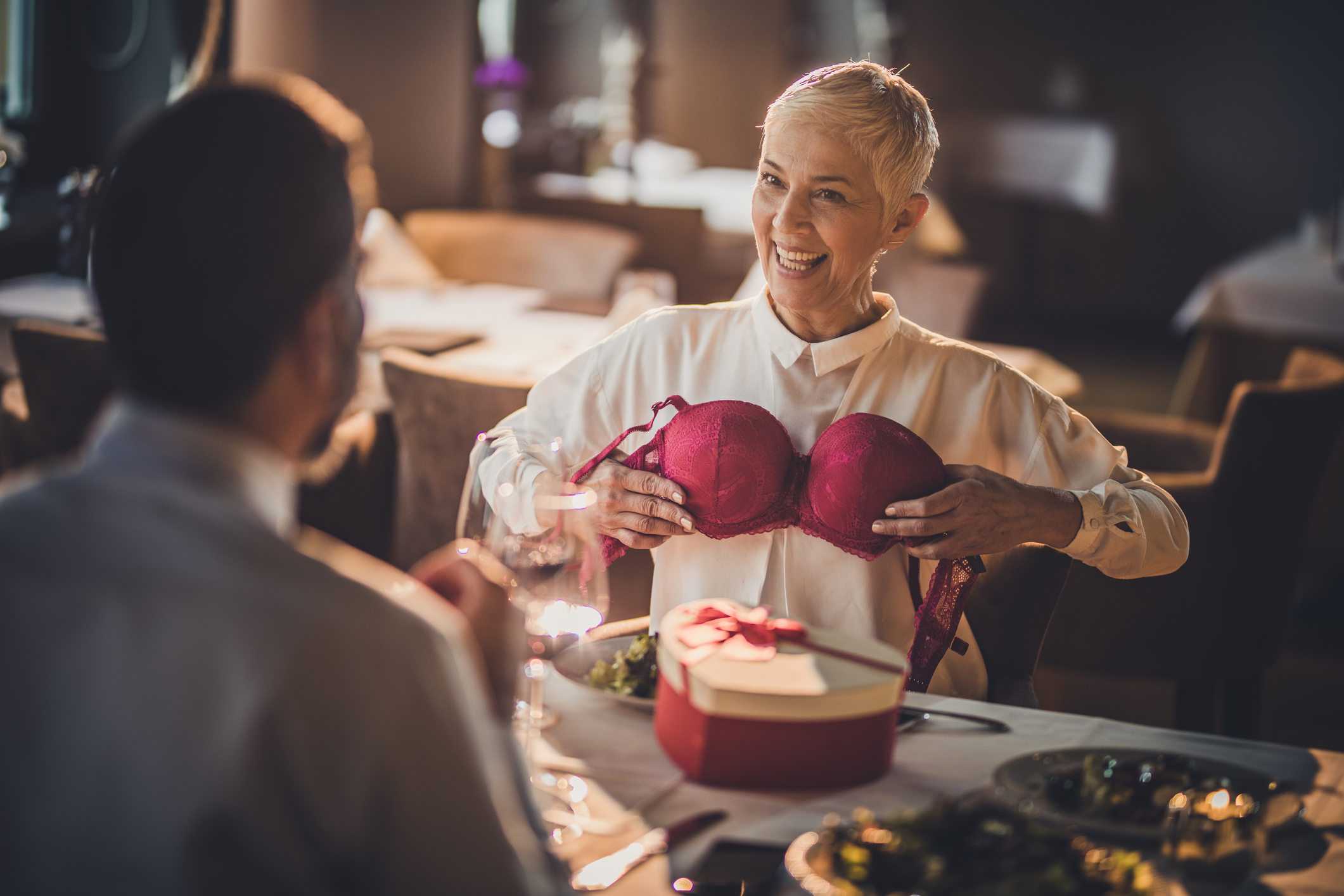 Playful senior woman having fun with her husband in a restaurant while trying on a bra he bought her.