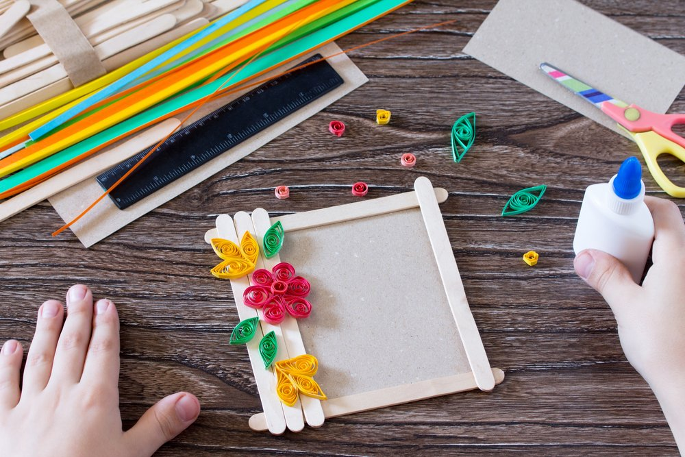 The child glues the details to a gift photo frame made of wooden sticks.