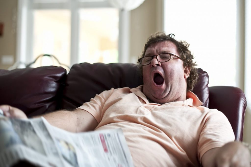 obese man yawning on the couch