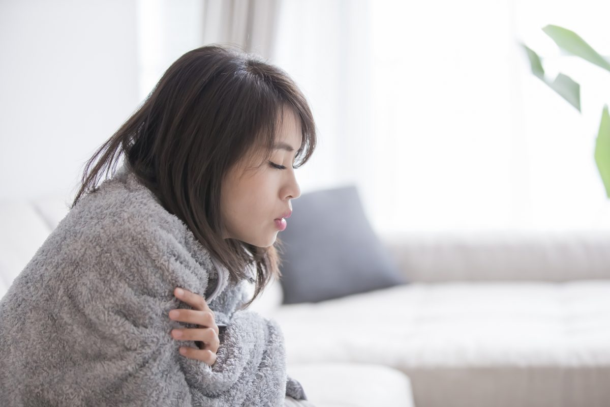 woman shivering in blanket