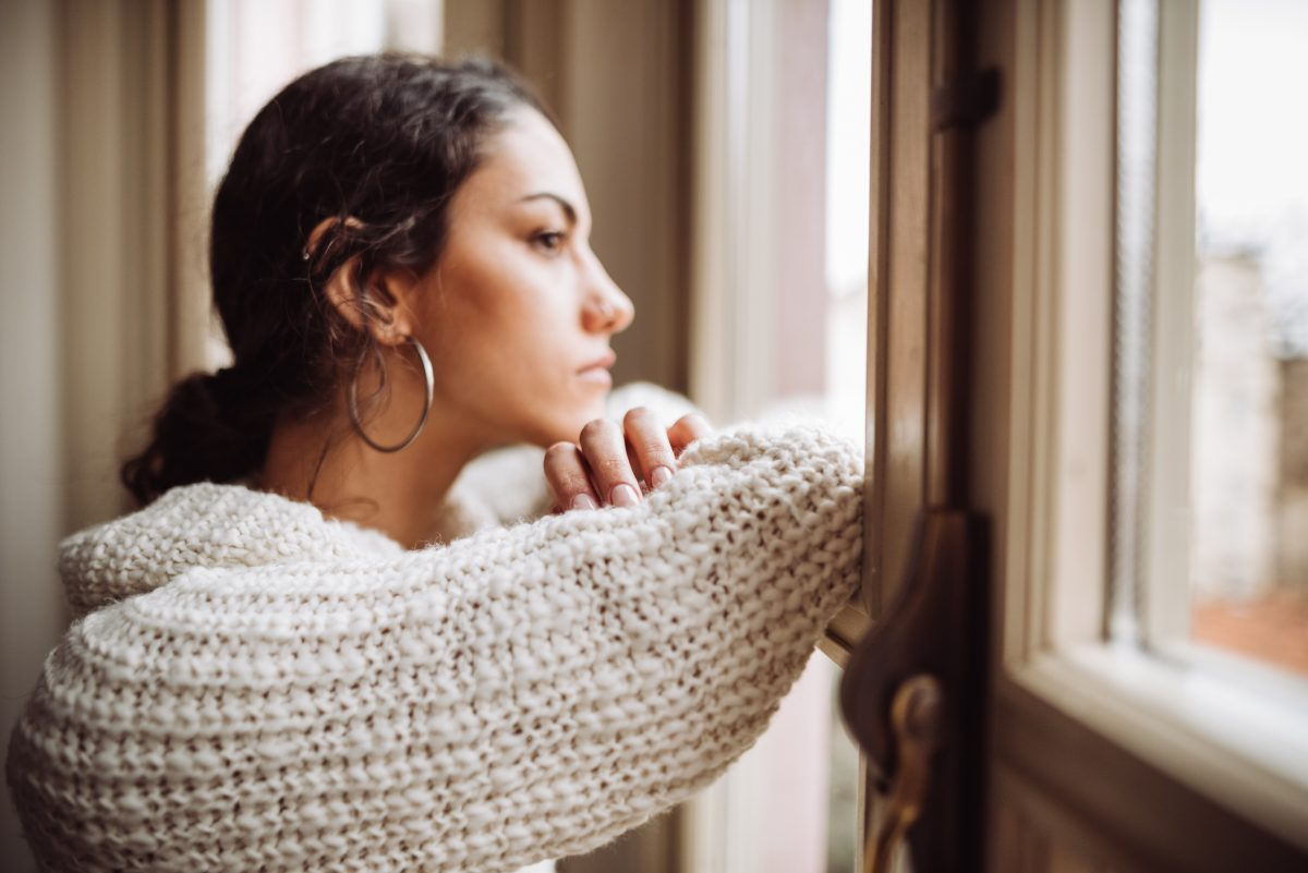 woman staring pensively out window