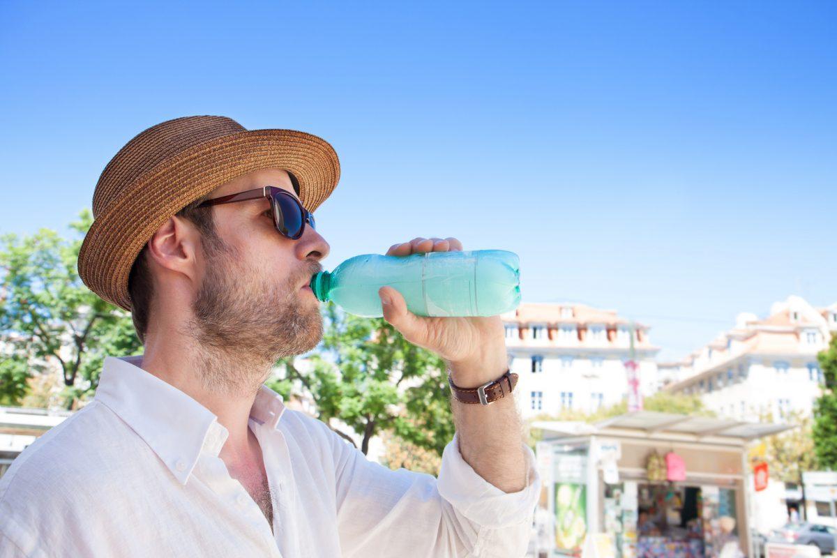 man in hat drinking water