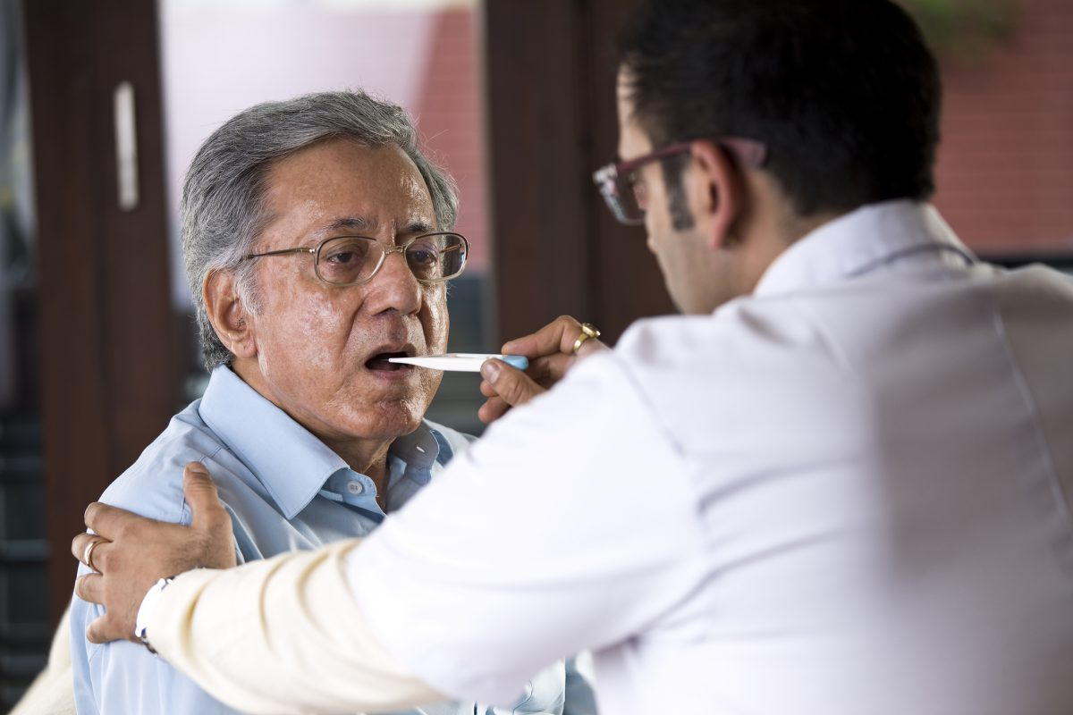 doctor checking man's temperature