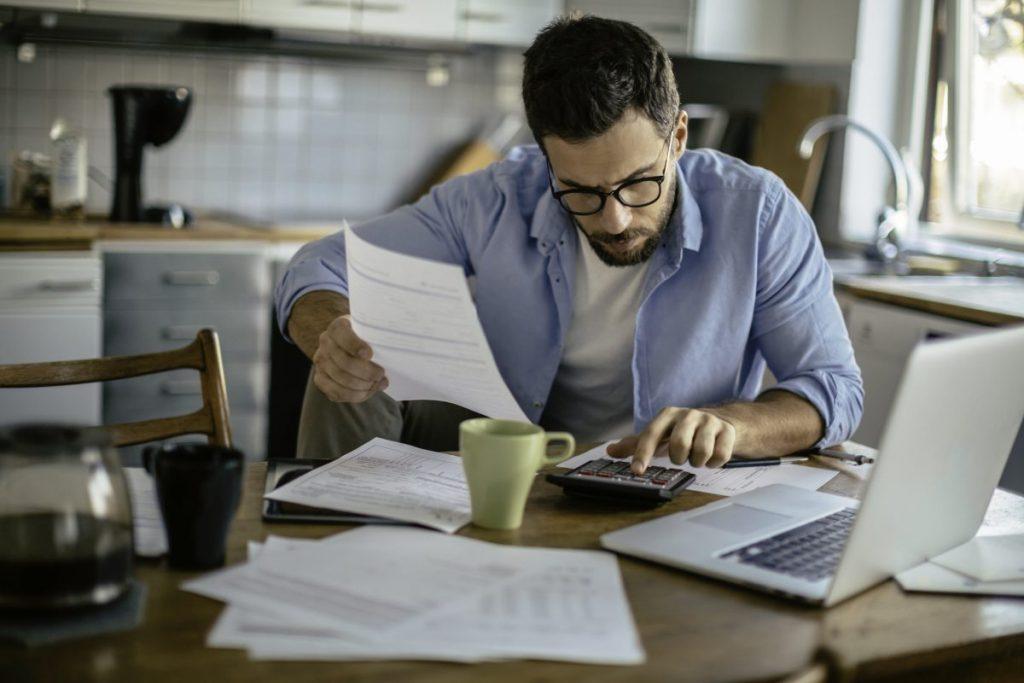 man working paperwork home kitchen