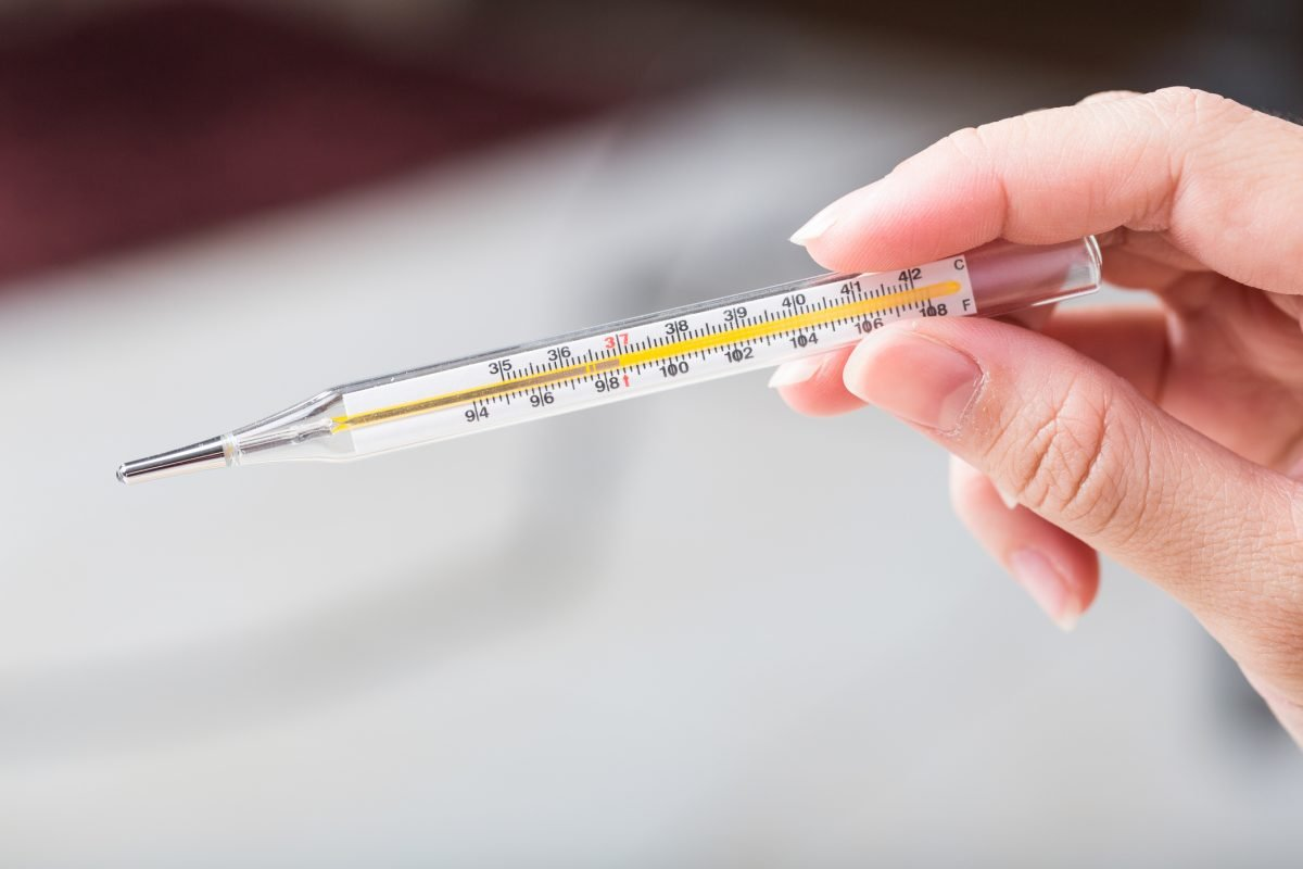 hand holding glass thermometer