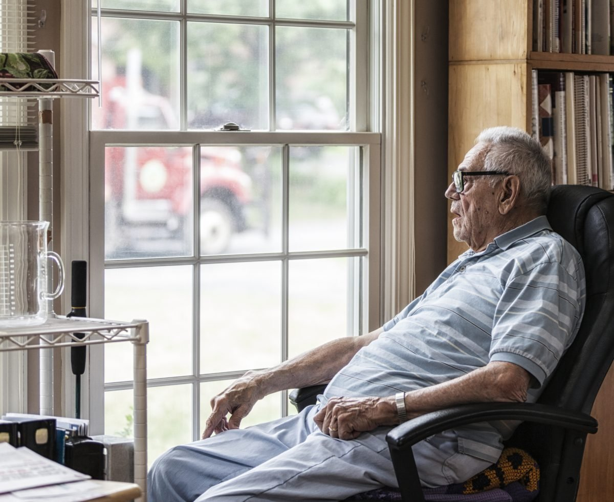 Elderly man sitting looking out of window