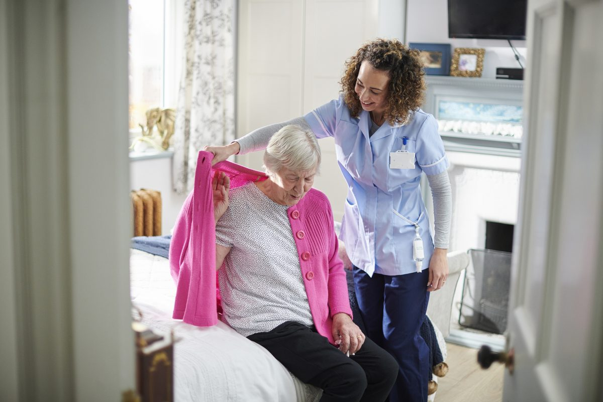 Carer helping lady dress