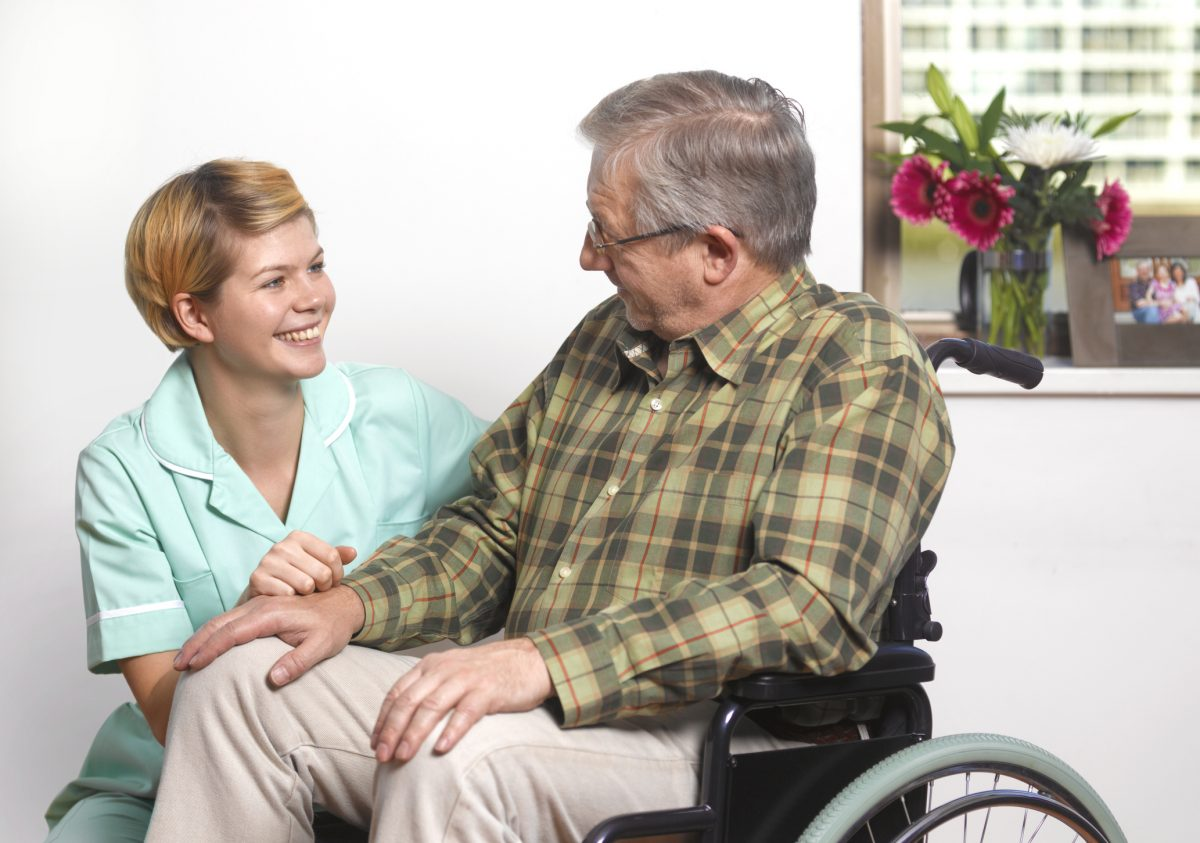 Man in a wheelchair with carer