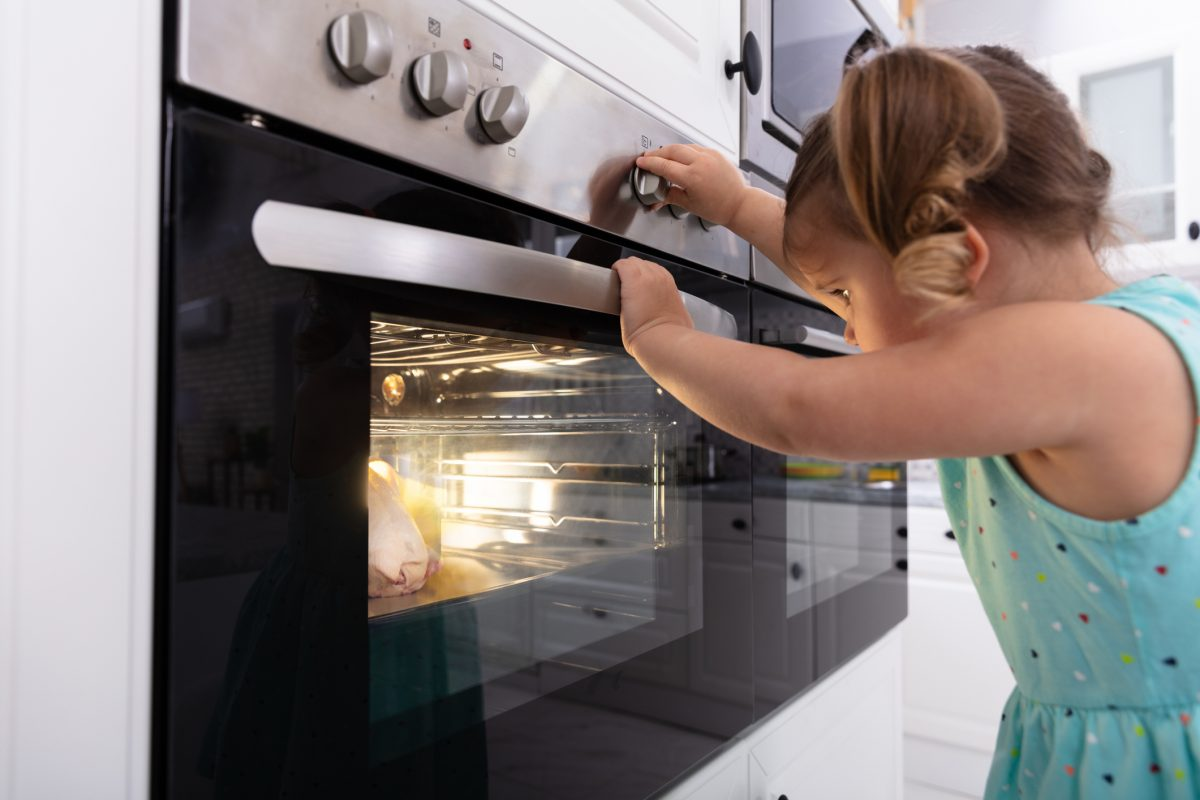 small girl touching oven