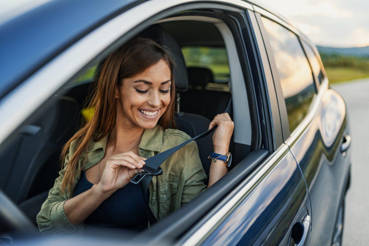 woman putting on seat belt