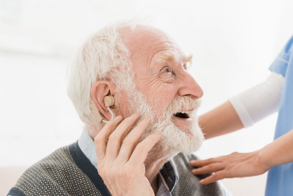 elderly man with hearing aid.