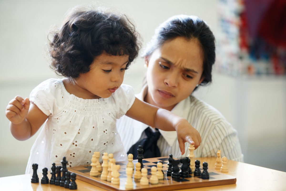 Toddler playing chess with mother