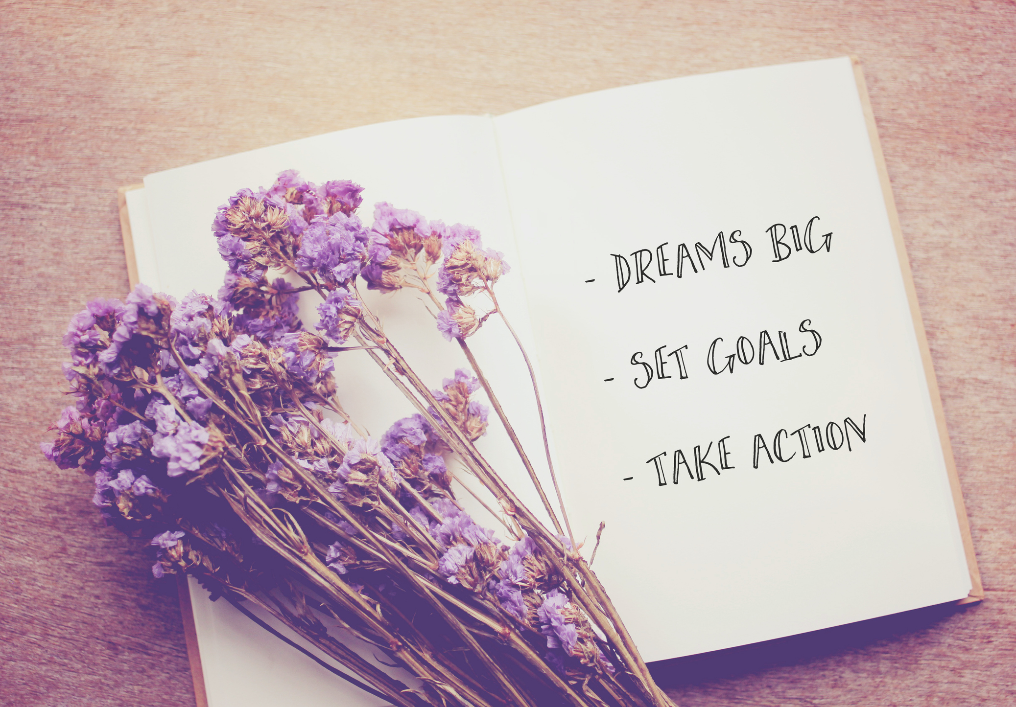 Inspirational quote on notebook and dried statice flowers with retro filter effect