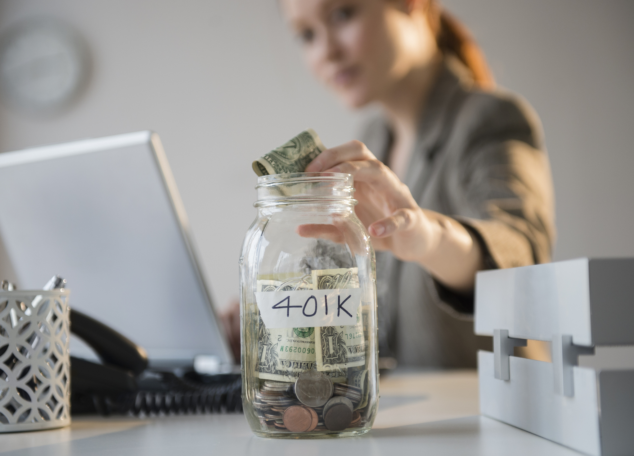 Businesswoman putting money into 401K jar at desk