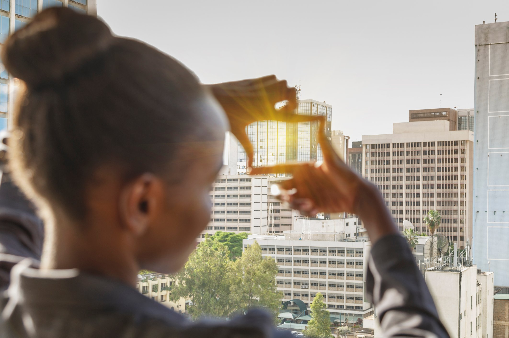 A young african business woman framing a building downtown Nairobi with her fingers
