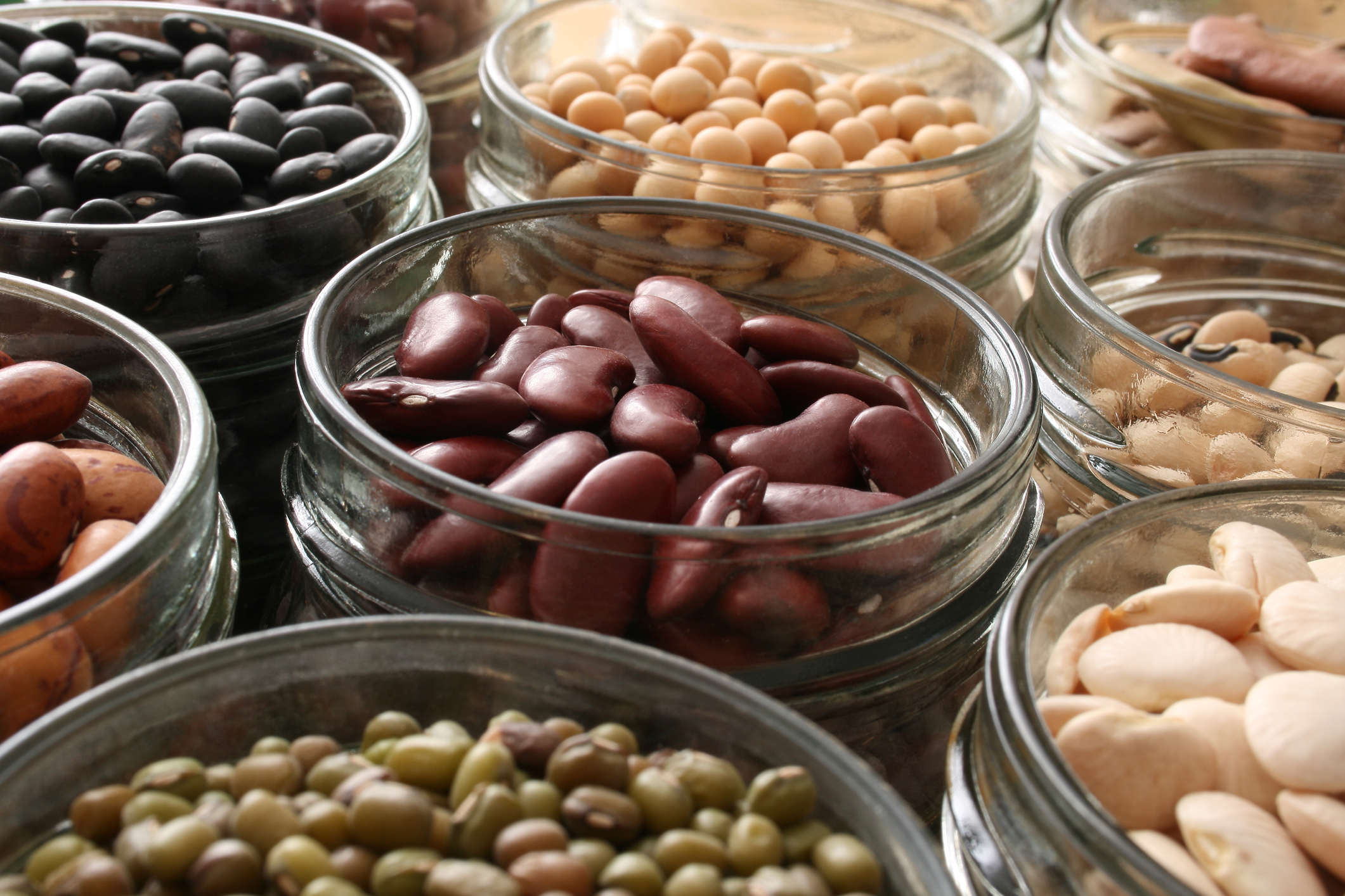 Variety of beans inside jars. Shallow depth of field