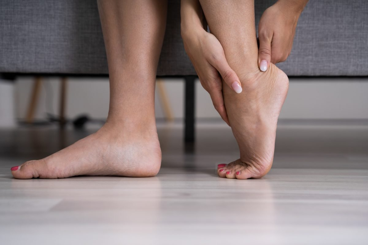 woman rubbing achilles tendon