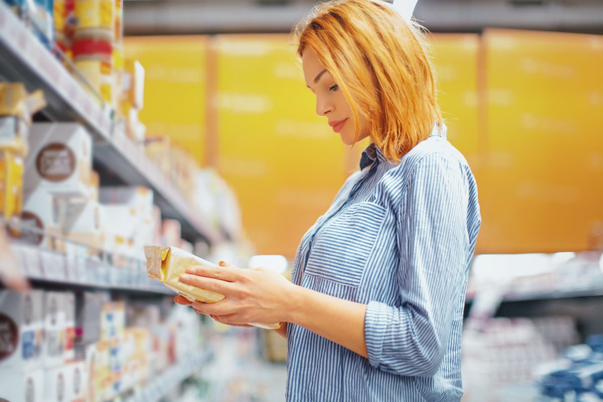 woman buying cereals checking label