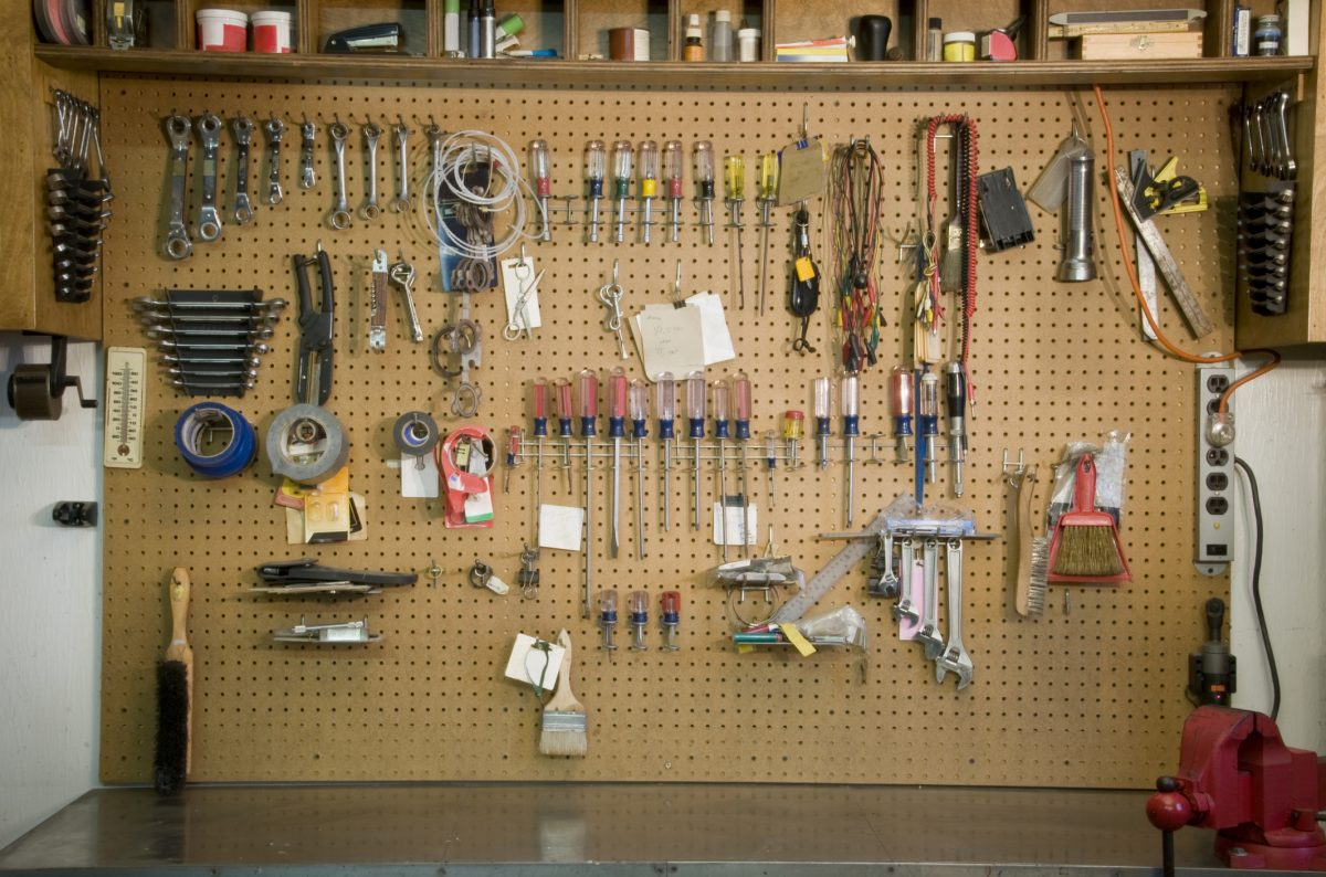 Pegboard is the classic way to store small items above a garage work bench.