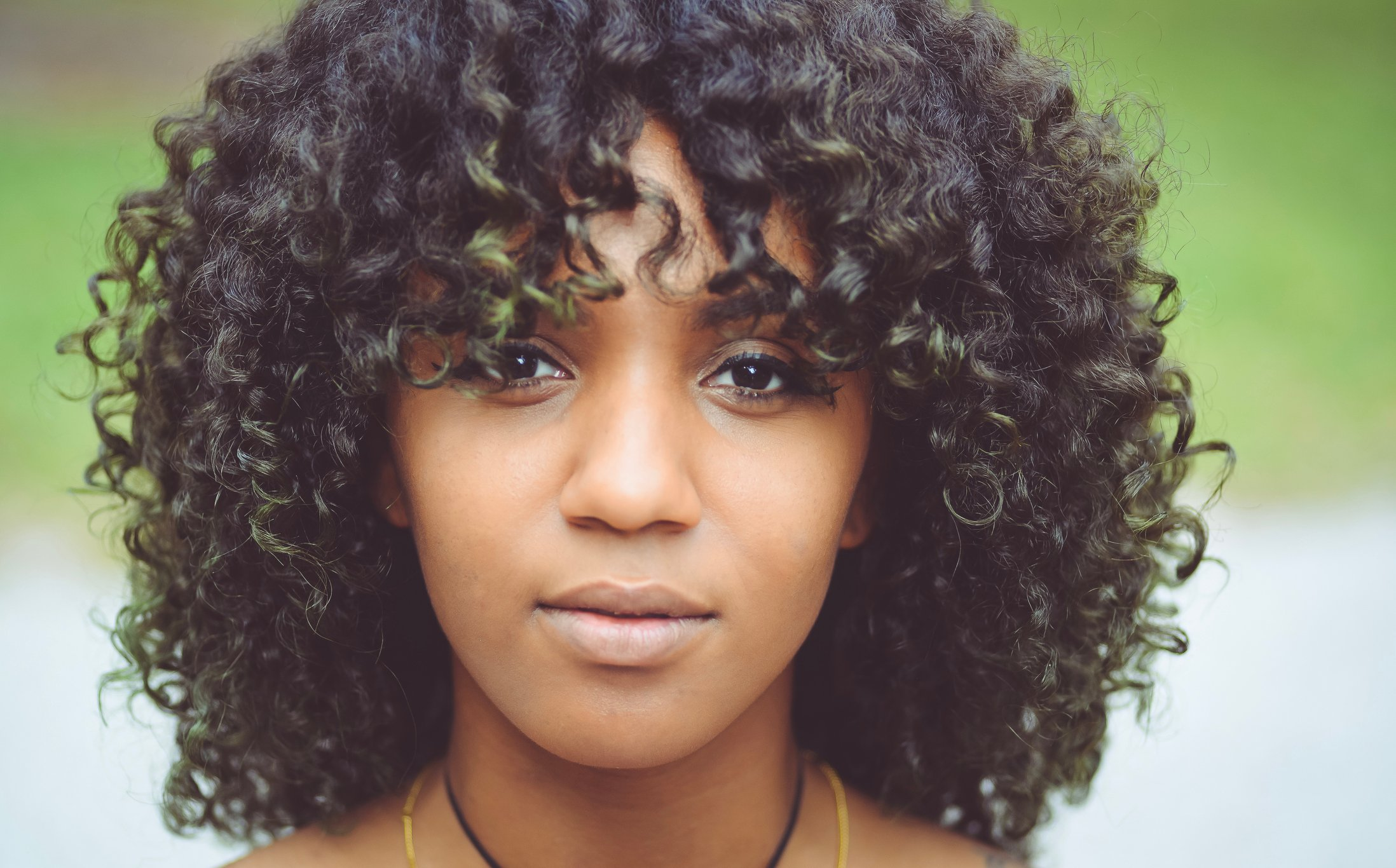 Close up of a young African American woman looking at the camera. Outdoors. Natural curly hair.