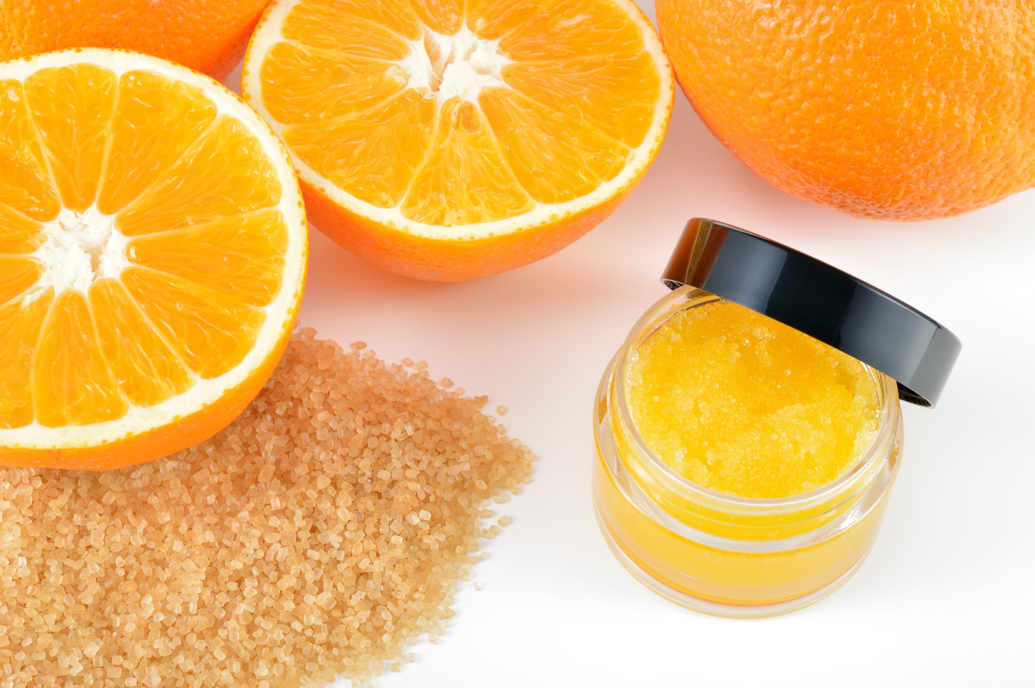 Natural orange sugar lip scrub on white background with reflection. Orange cosmetic in a glass jar with oranges in a background.