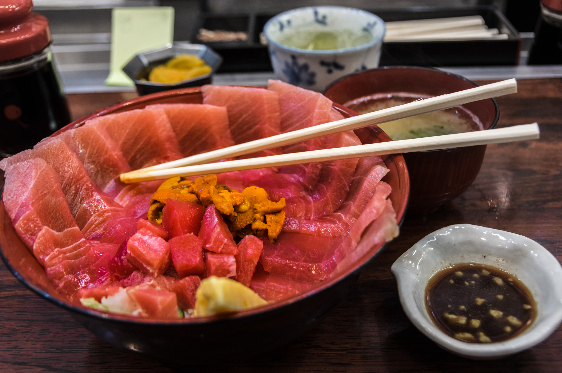 A bowl of raw tuna is served at a Japanese restaurant with miso soup and soy sauce.