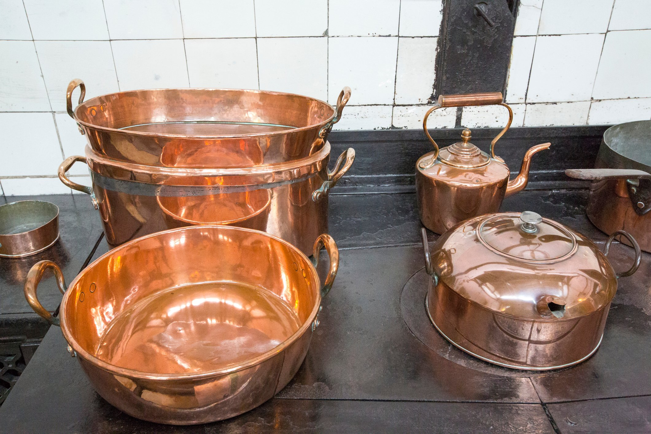 Copper pots and pans in the kitchen at Lanhydrock a country residence dating from the 1600's in Cornwall, UK.