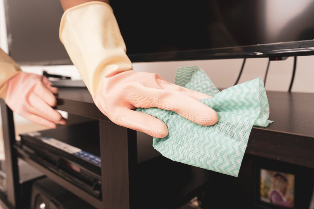 women cleaning the television cabinet, close up.