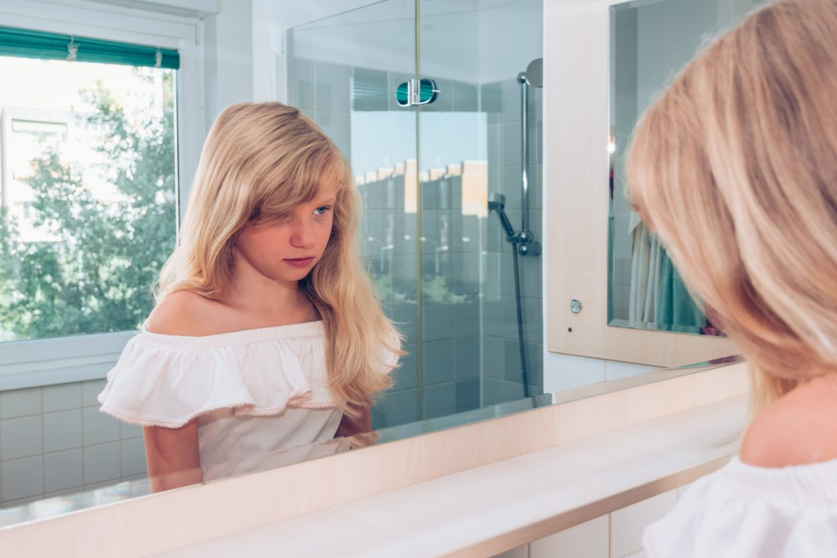 unhappy child looking in mirror
