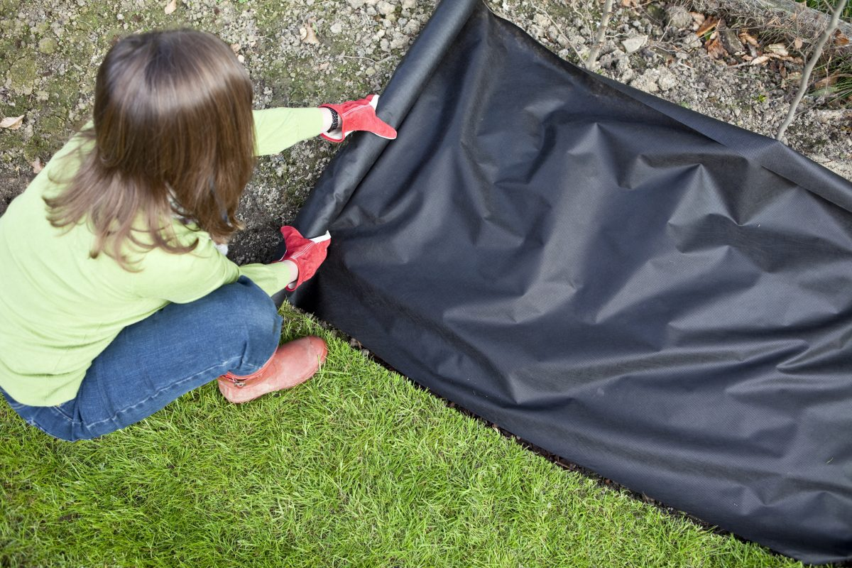 Cut weed barrier fabric for herbs