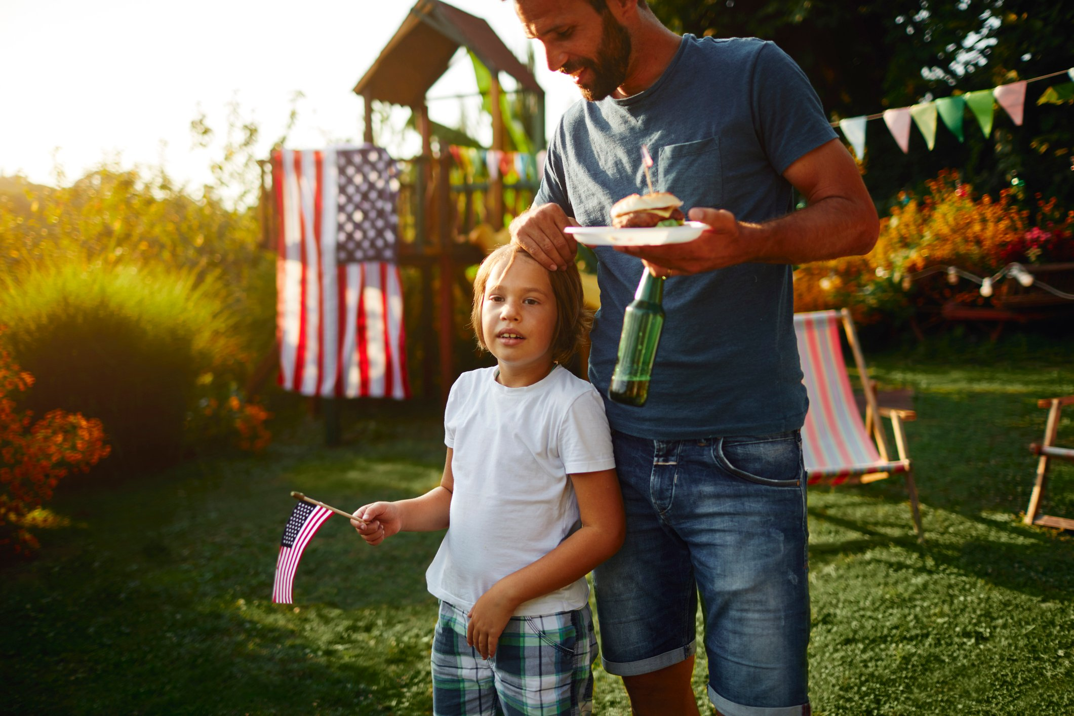 Family on picnic in back yard celebrating 4th of July - Independence Day. Father holding burger and his son holding american flag.
