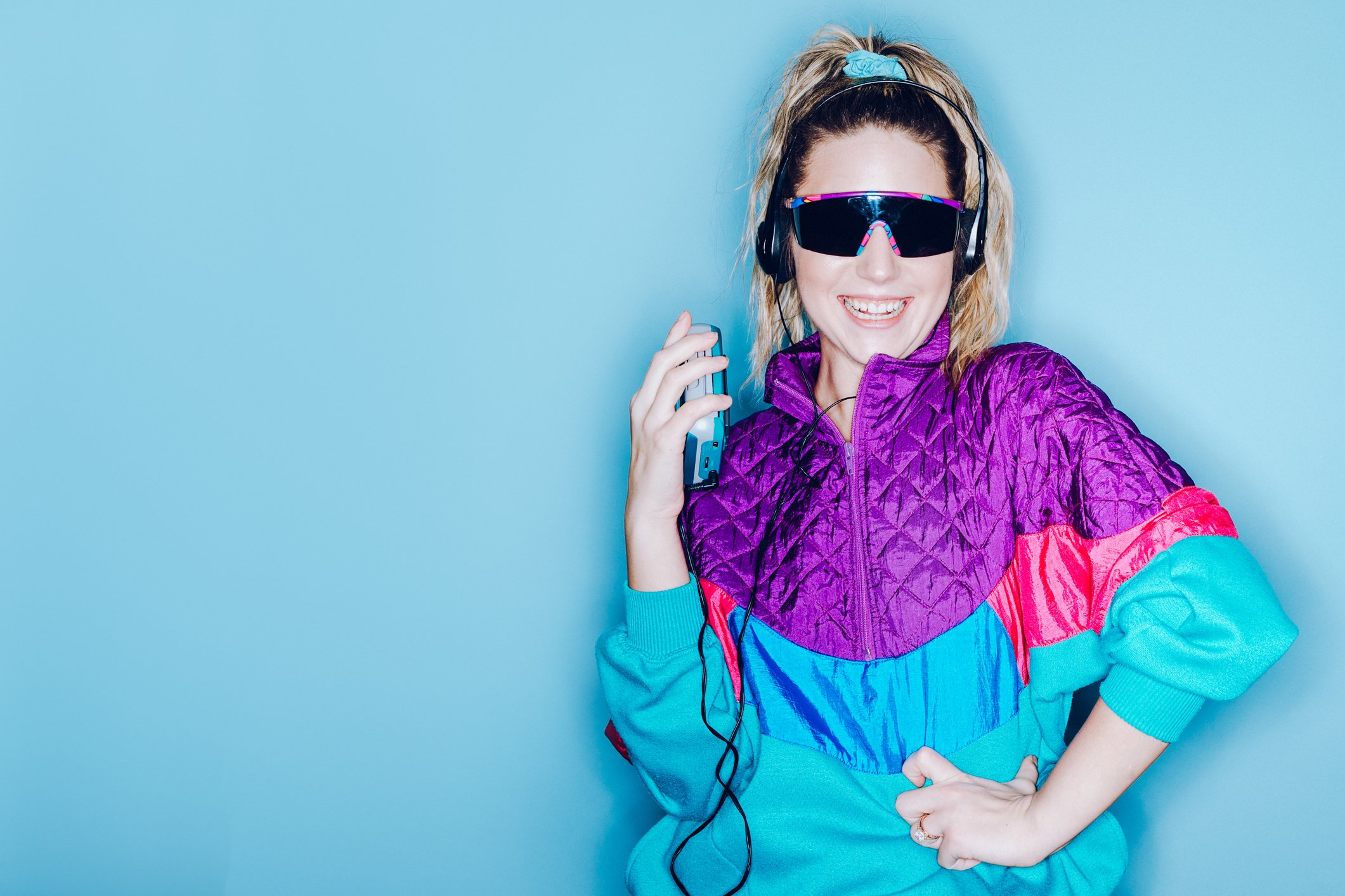 A woman wearing clothing styled after the 1980's and 1990's listens to music on her personal cassette tape player in front of a large bright blue background. Shot with a ring flash.