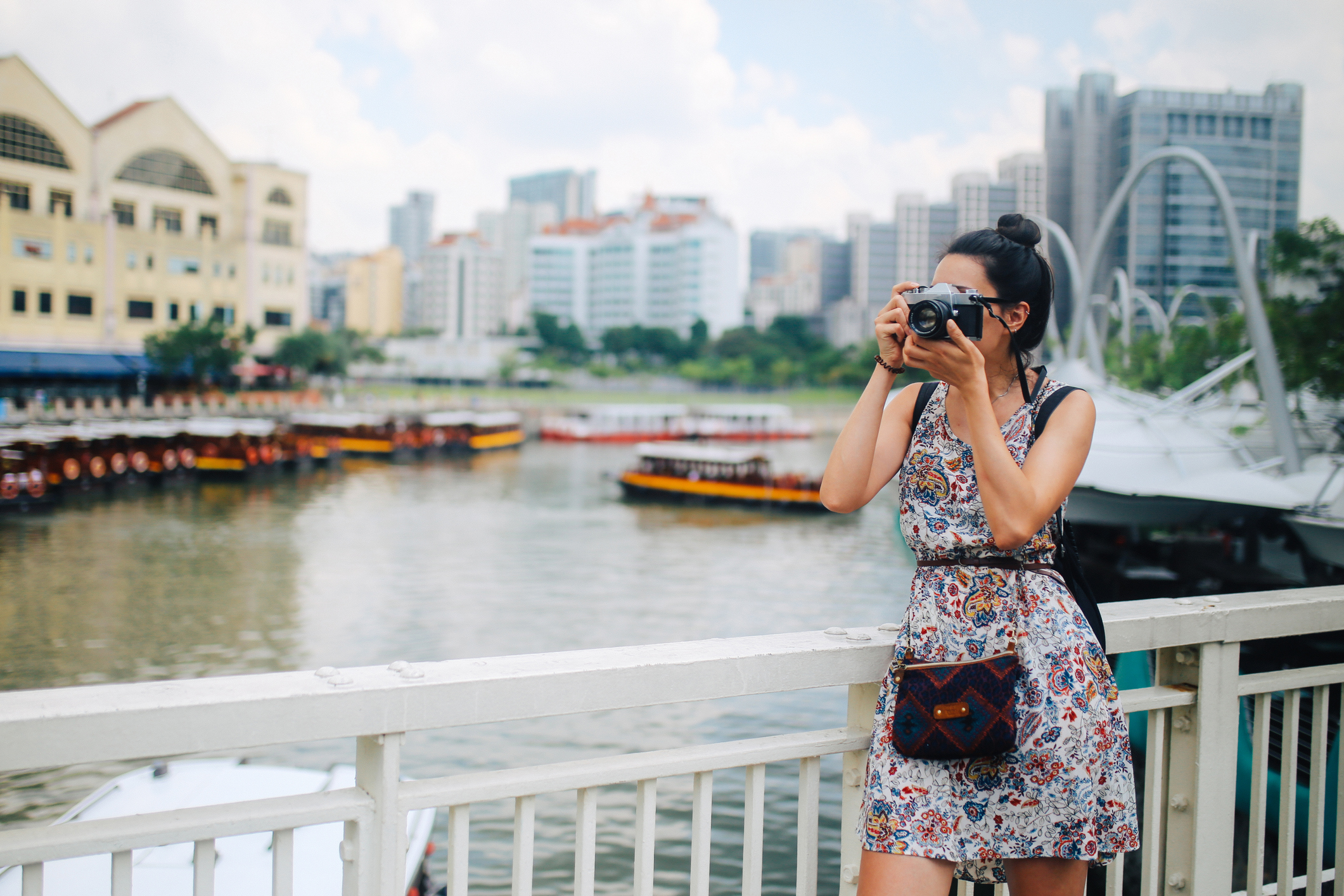 Image of a young fashionable brunette woman. She is relaxing after a day of long walks, wearing a casual but fashionable dress, enjoying the beautiful day on the busy streets of Singapore, taking images with her retro looking mirrorless camera or a true 35mm analog SLR.