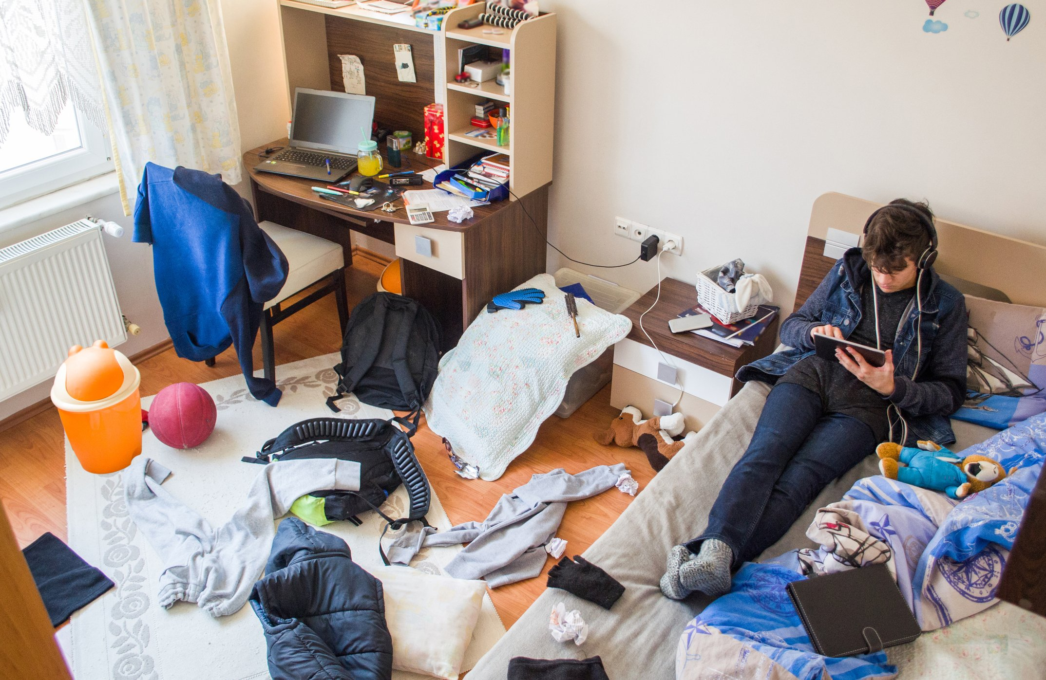 Teenager is using tablet in his messy room