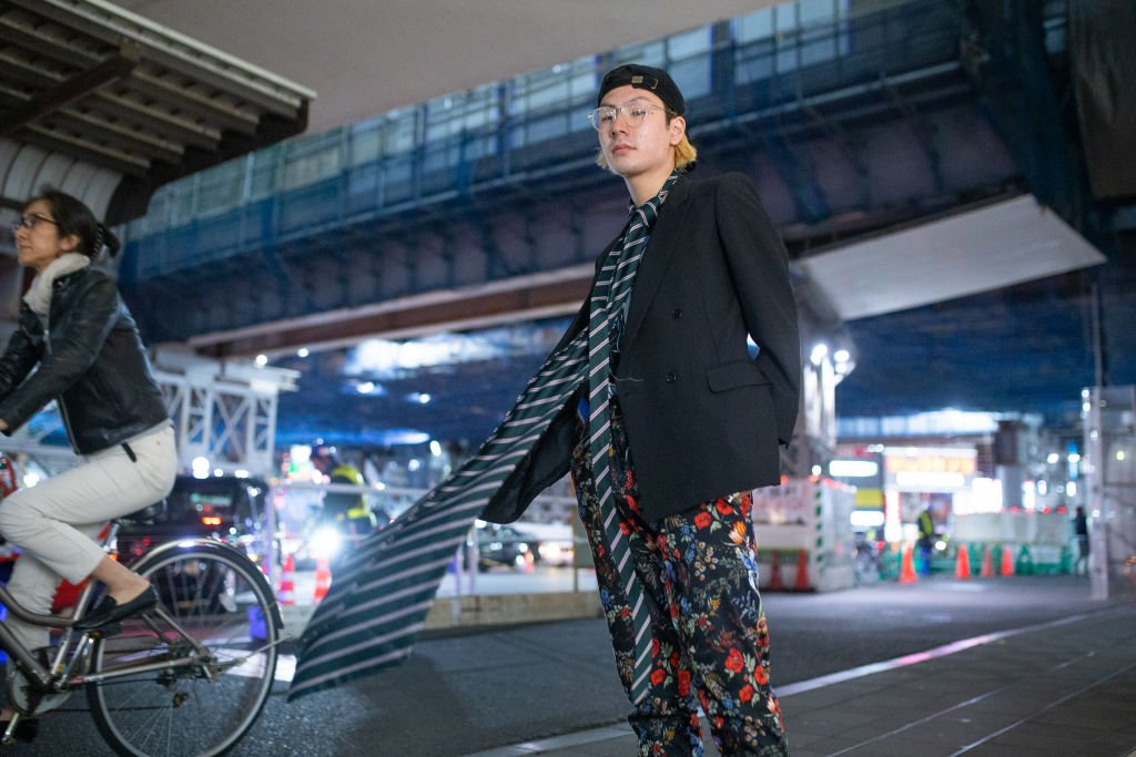 TOKYO, JAPAN - MARCH 22: A guest is seen wearing oversized striped tie, floral pants, black blazer and cap during the Amazon Fashion Week TOKYO 2019 A/W on March 22, 2019 in Tokyo, Japan.
