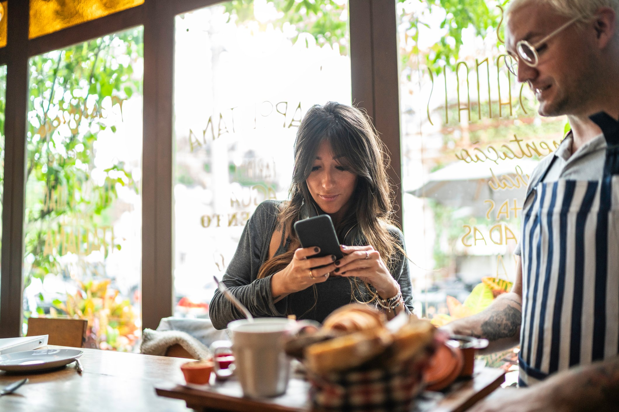 Woman taking photos of her food for social media, waiter by her side