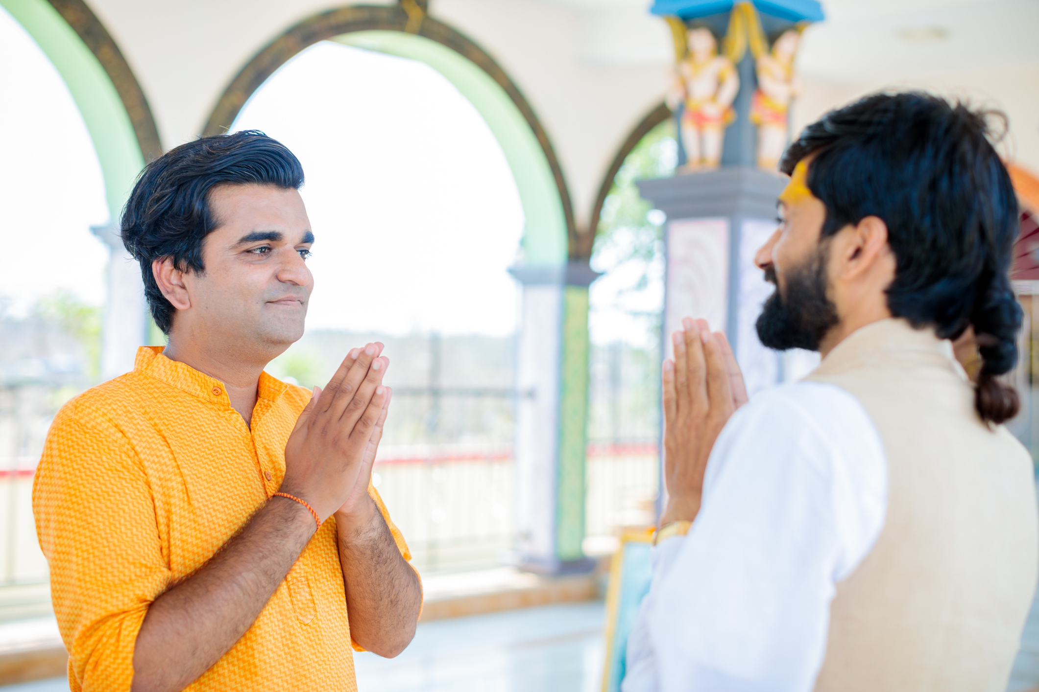 Temple Visitor and Hindu Priest Greeting Each Other