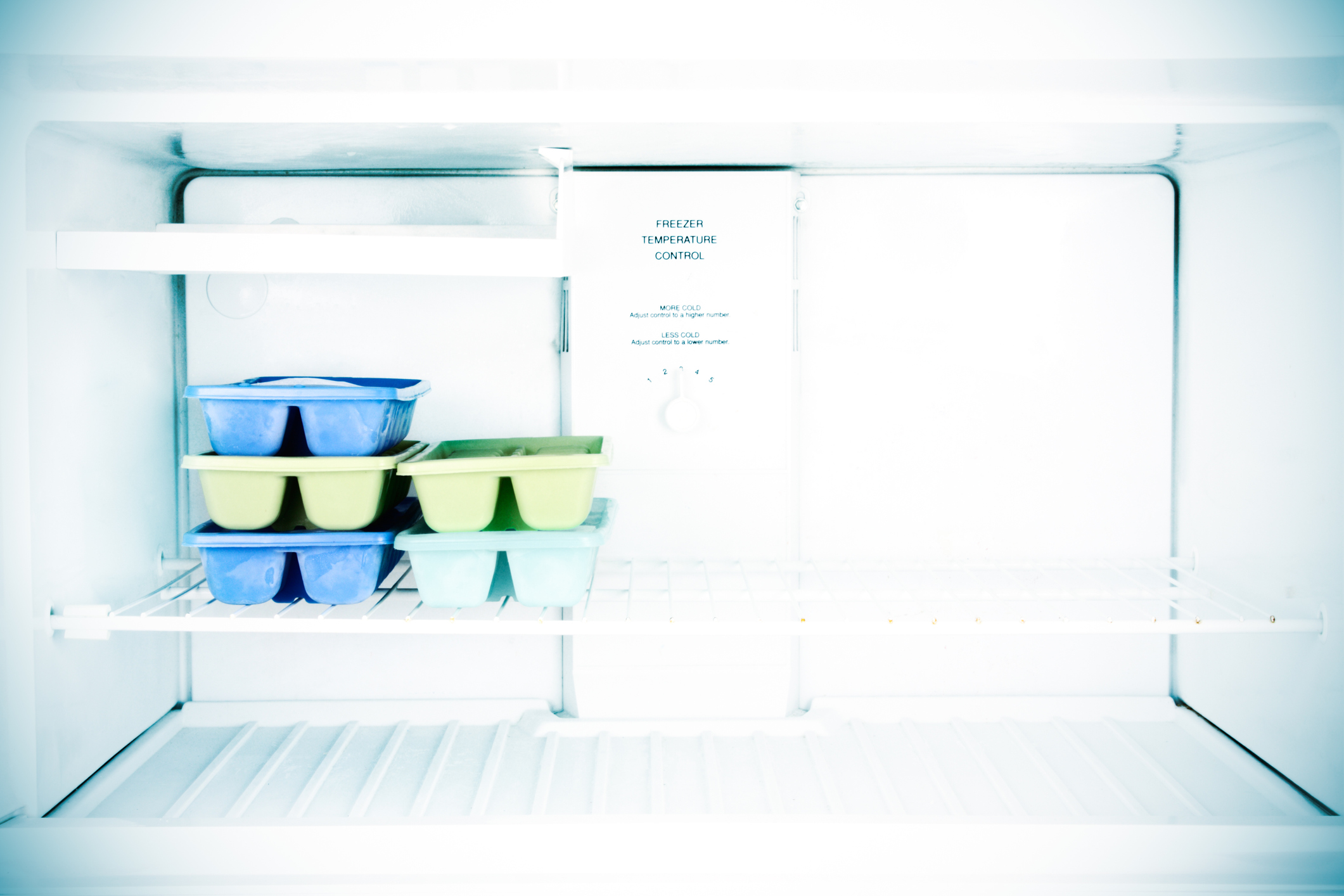Ice cube trays sit in a freezer.