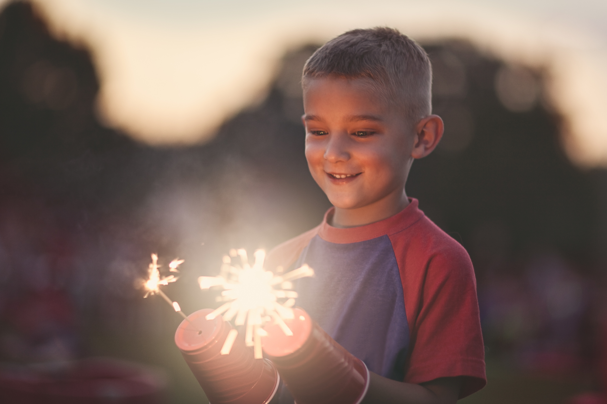 Cute, little boy holding two Fourth of July sparklers at dusk.