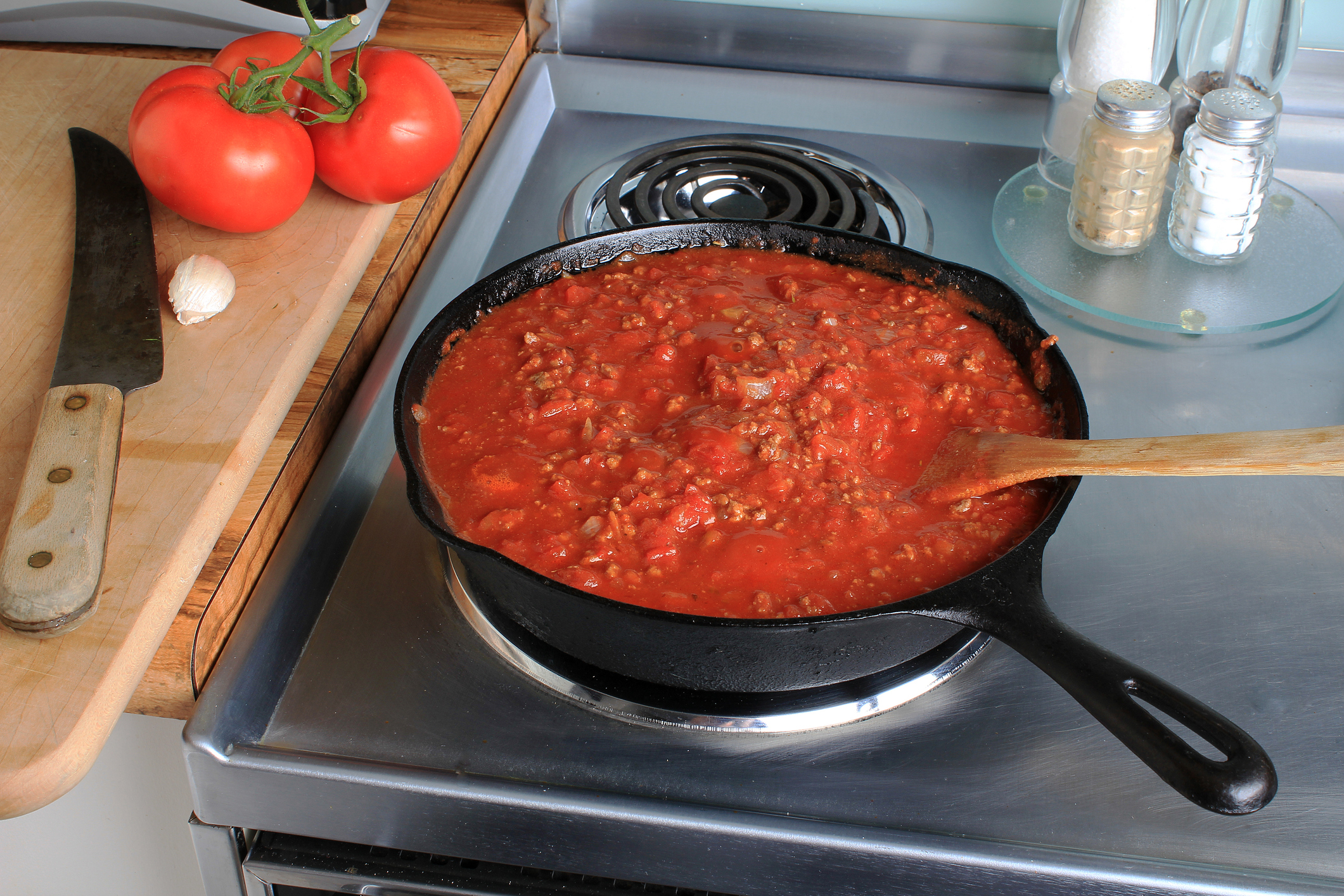 Tomato and Meat Spaghetti Sauce simmering in cast iron skillet atop Stainless Steel electric stove with tomatoes and garlic on cutting board with large kitchen knife.