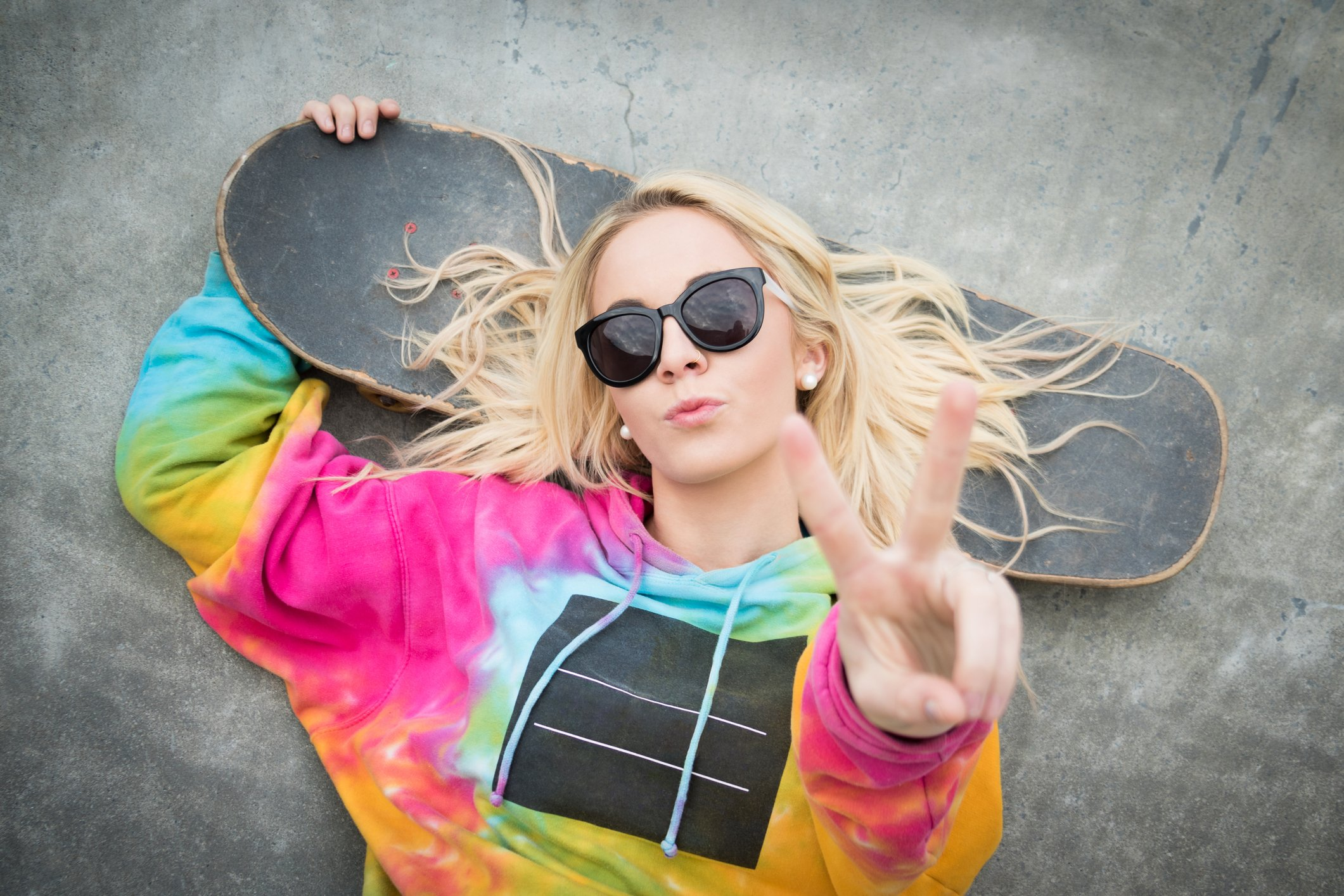 Pretty blond skater girl giving peace sign