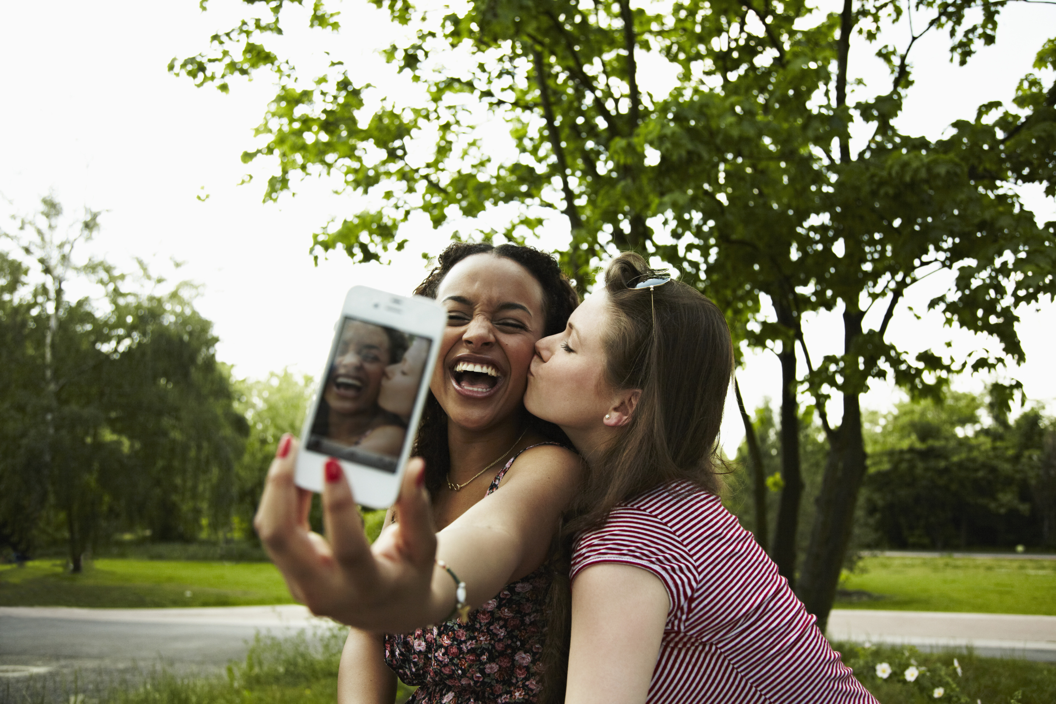 two young adult woman taking a self-portrait with a mobile phone and fooling around making faces.