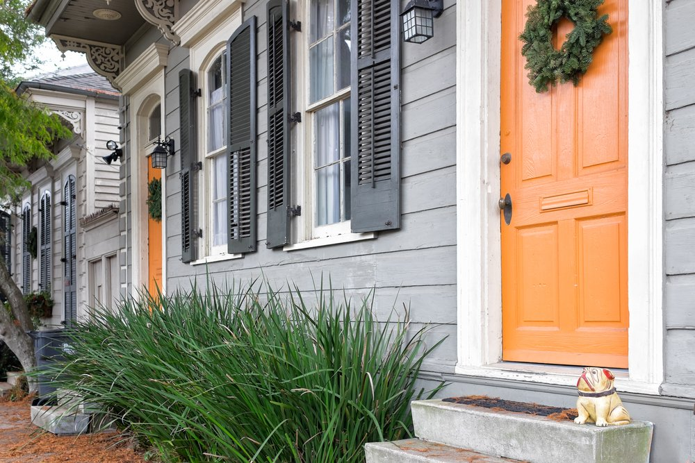 New Orleans quaint shotgun houses with gingerbread trim and front doors painted orange.