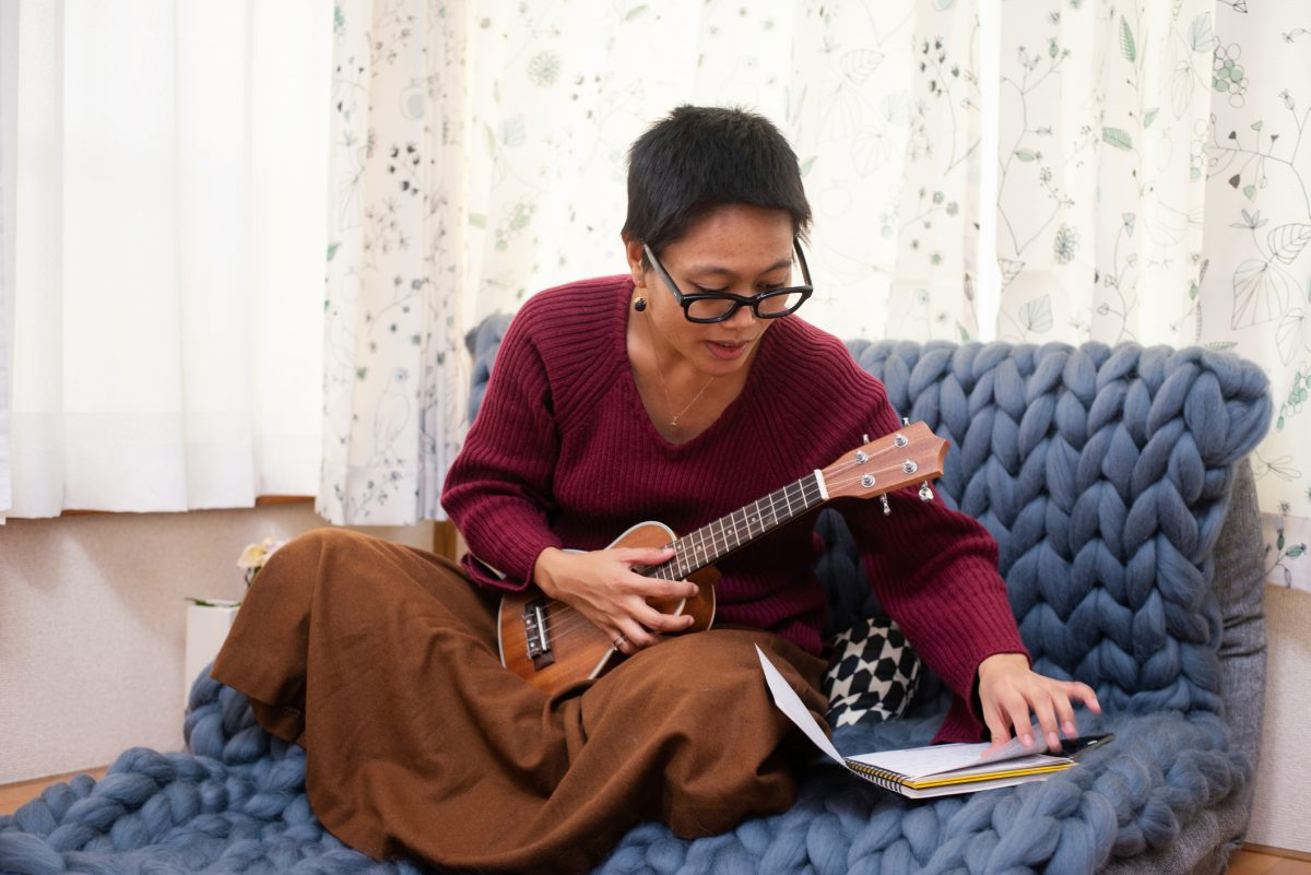 A woman sitting on a couch with a ukulele.